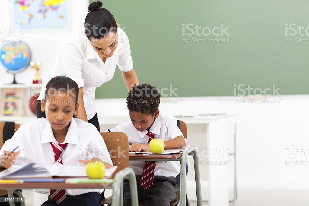 caring elementary school teacher and students stock photo