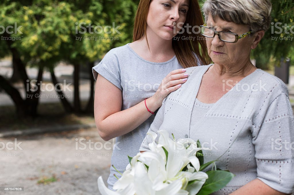 Caring granddaughter supporting her grandma stock photo