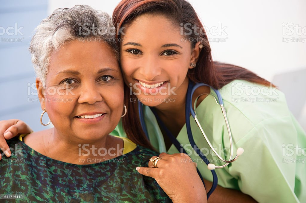 Caring, mixed-race nurse and senior adult patient in hospital. stock photo