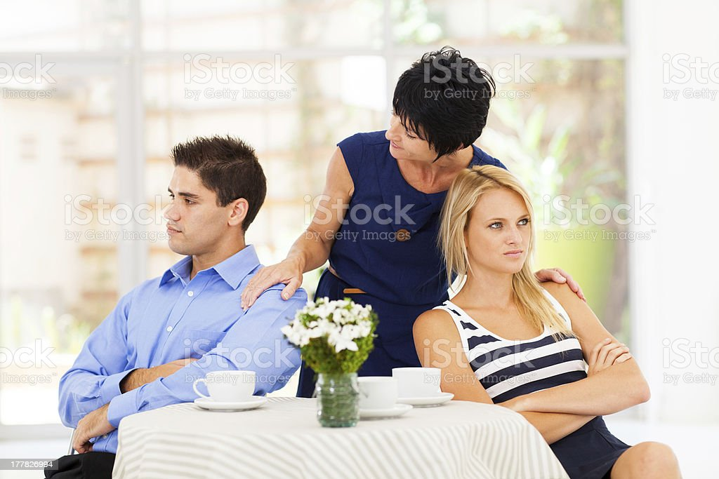 caring mother reconciling fighting couple stock photo