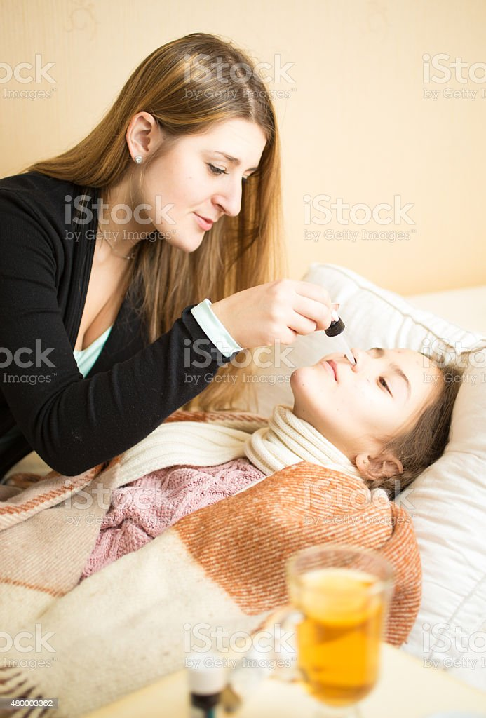 caring mother spraying daughters nose lying in bed stock photo