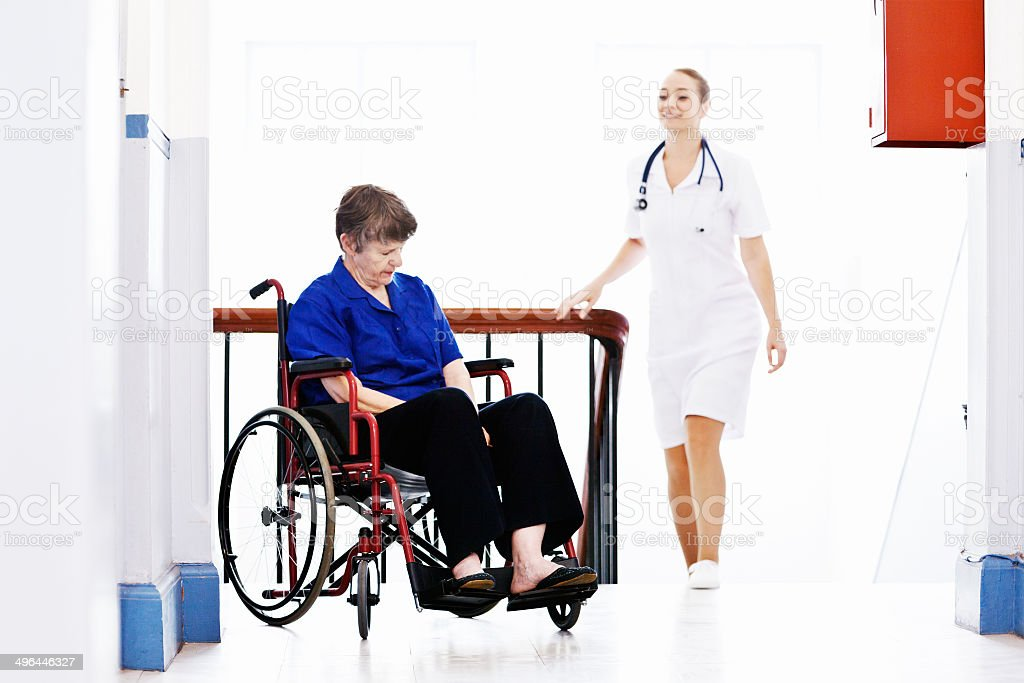 Caring, smiling nurse approaches sleeping patient in wheelchair royalty-free stock photo