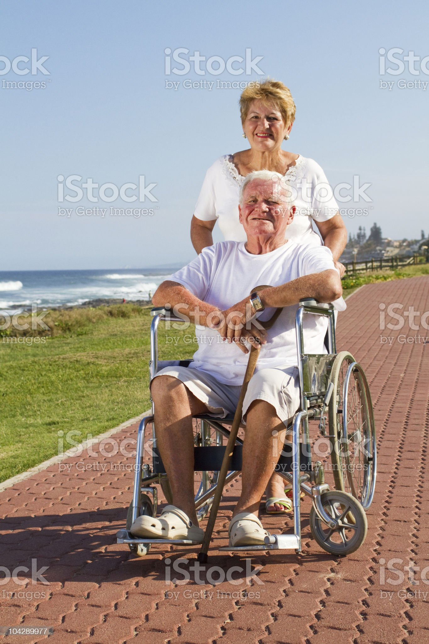 caring wife pushing husband on wheelchair royalty-free stock photo