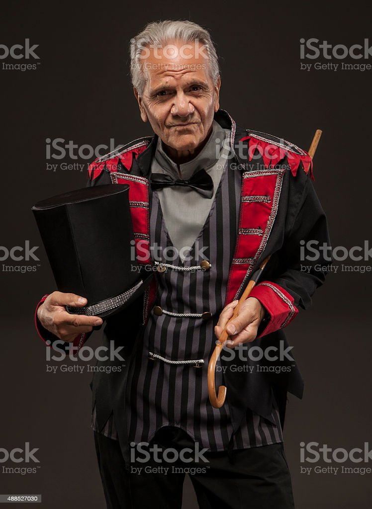 Carnival barker holding his cane and hat. stock photo