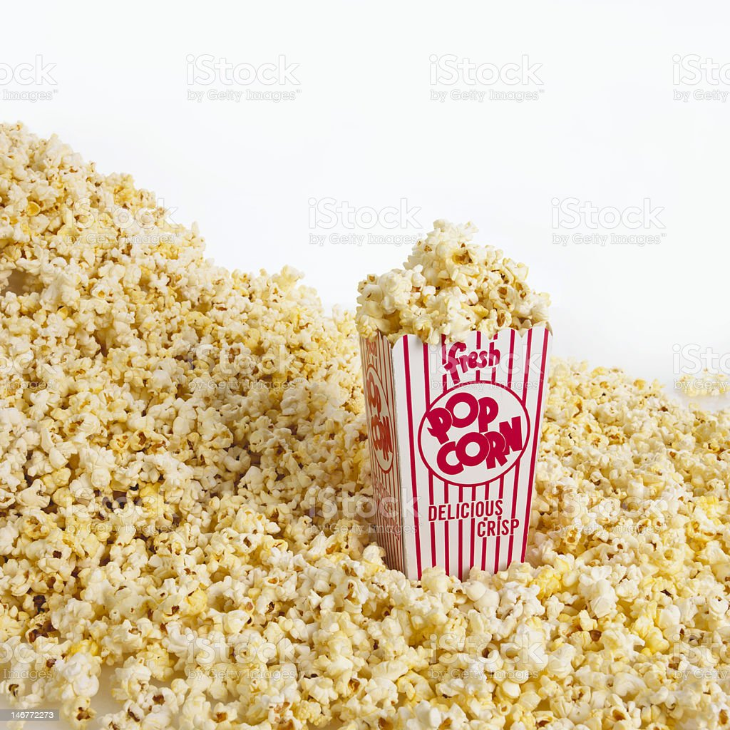 A carnival box of popcorn in a pile of popcorn stock photo