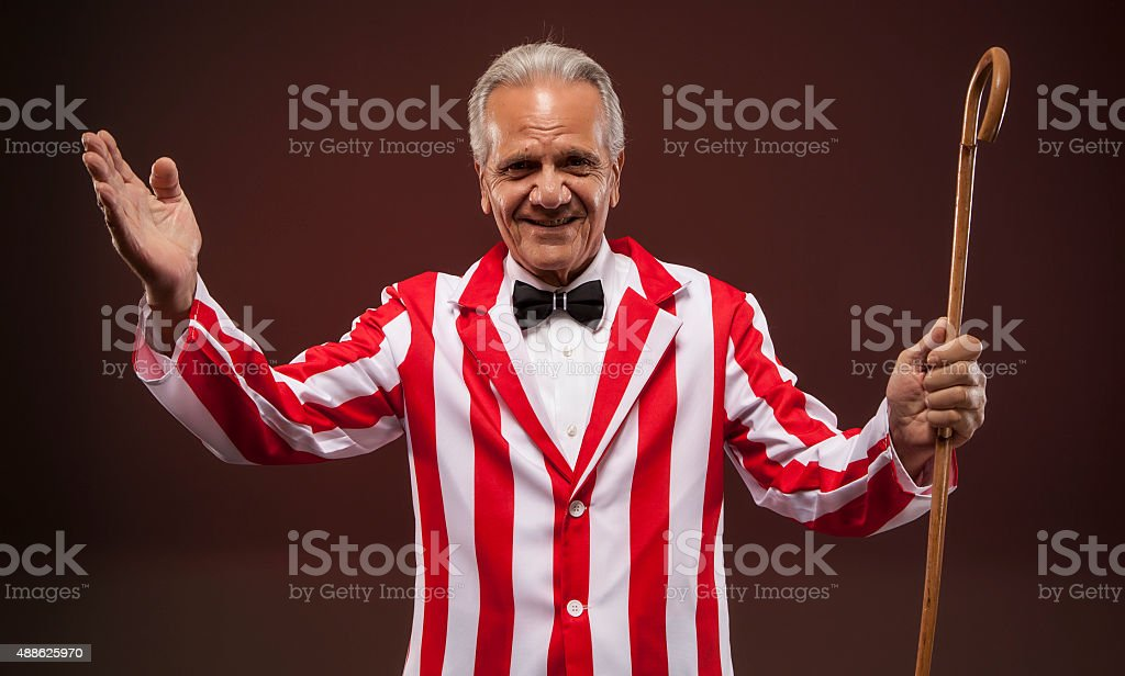 Carnival man looking straight forward with a cane. stock photo