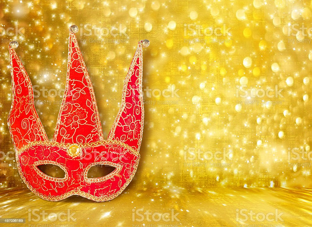 Carnival mask and a red Christmas ball on  golden background royalty-free stock photo