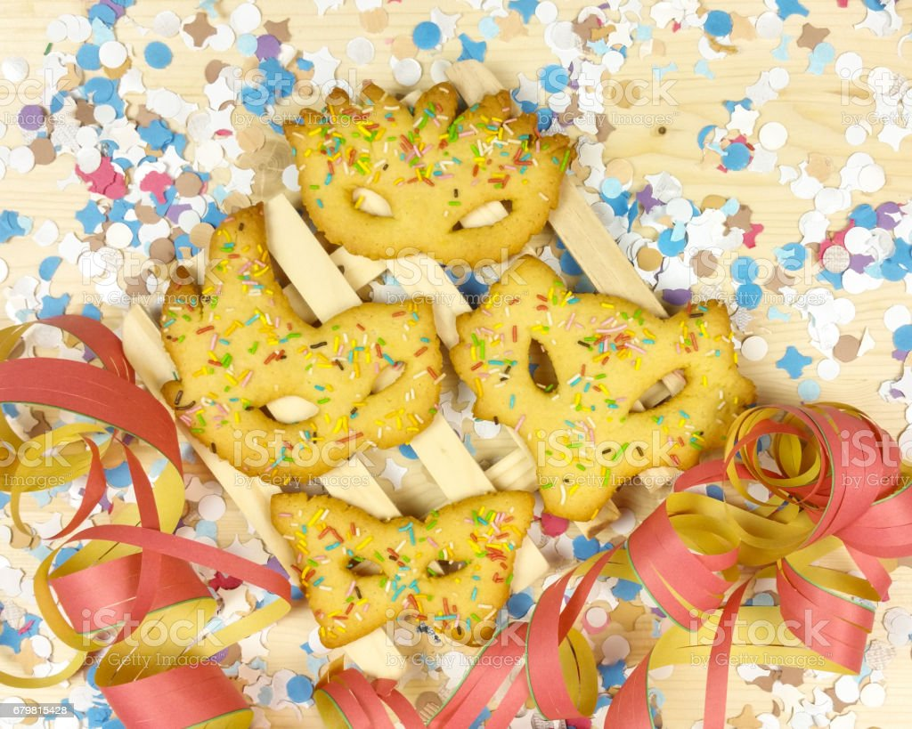 carnival masks of short pastry with streamers on wood background stock photo