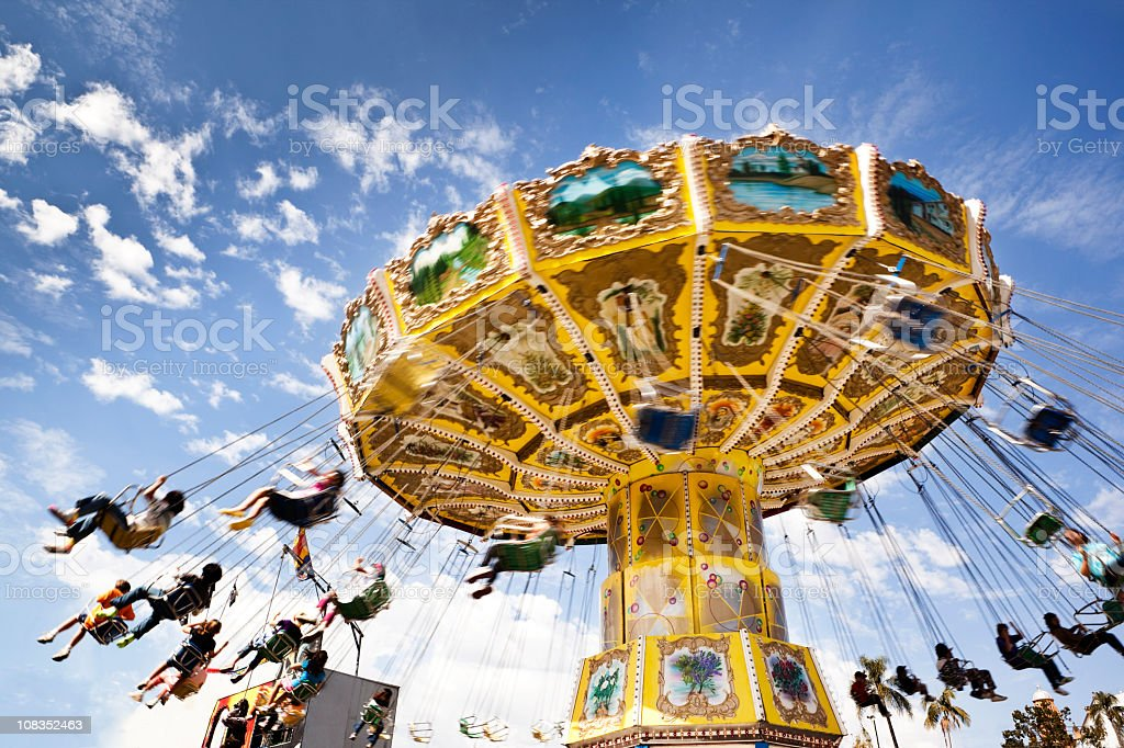 A carnival ride with swings in motion on a cloudy day stock photo