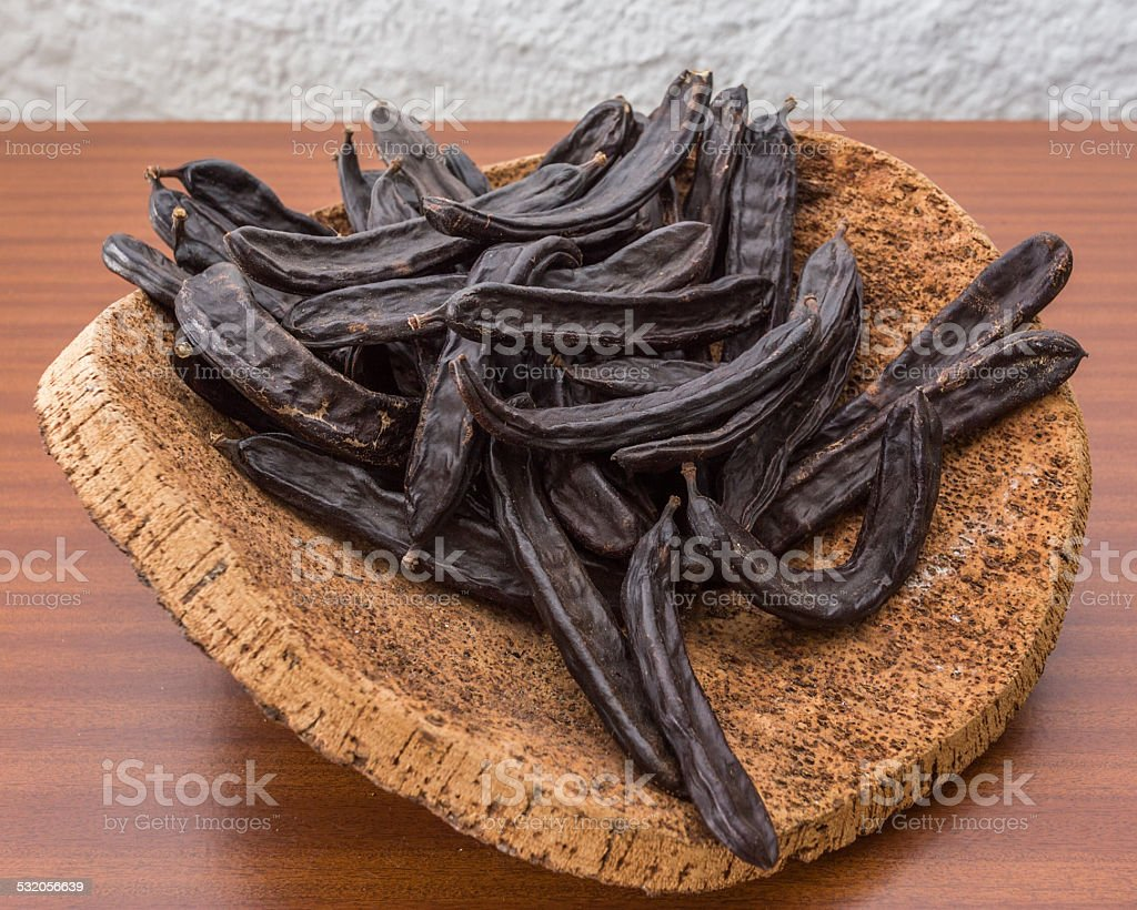Carob pods on cortical stand. On the table. stock photo