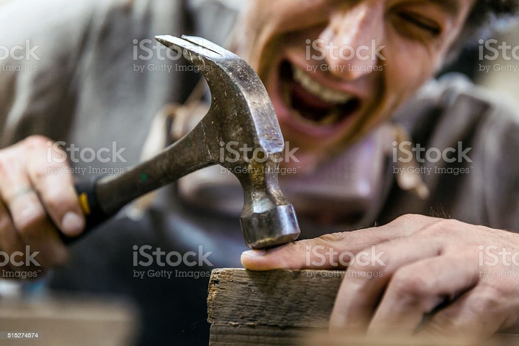 Carpenter accidentally hit his finger with hammer stock photo