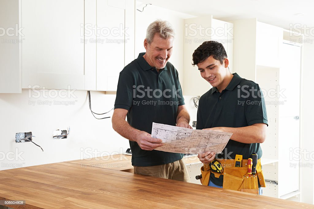 Carpenter And Apprentice Installing Luxury Fitted Kitchen stock photo