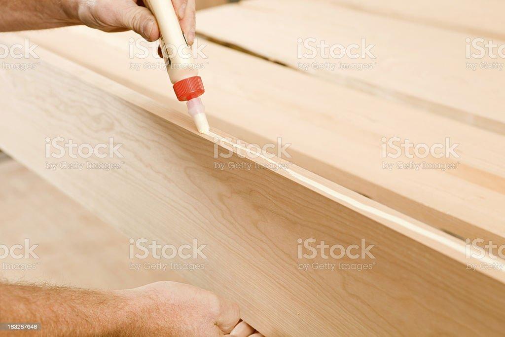 Carpenter applying Wood Glue to a Board stock photo