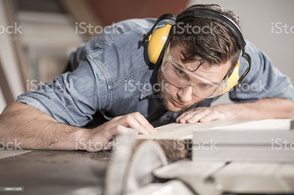 Carpenter at work with wood stock photo