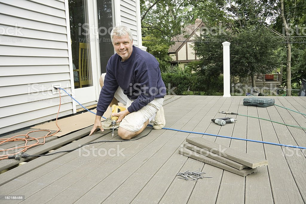 carpenter building a deck in the suburbs royalty-free stock photo