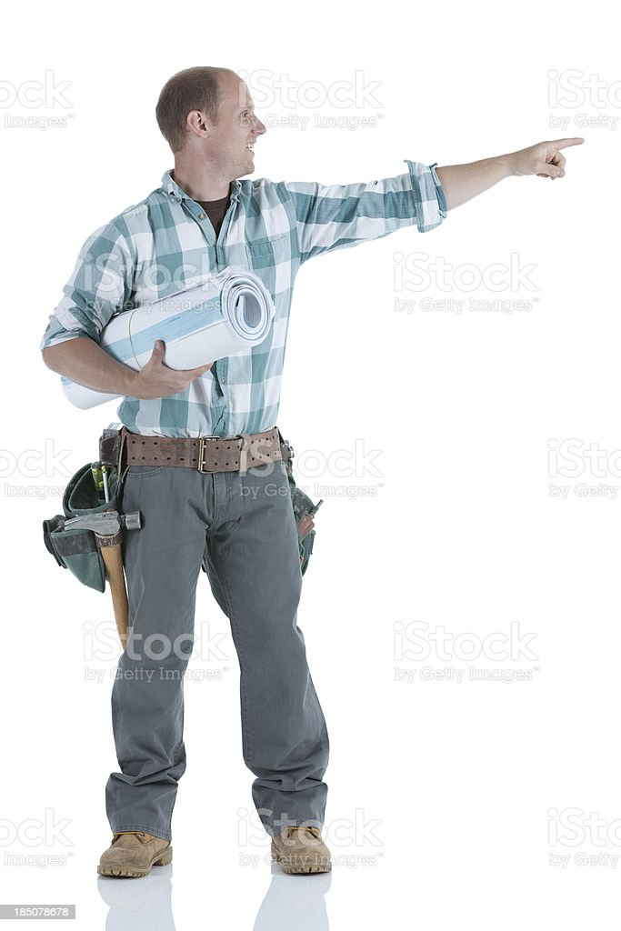 Carpenter carrying blueprint and pointing royalty-free stock photo