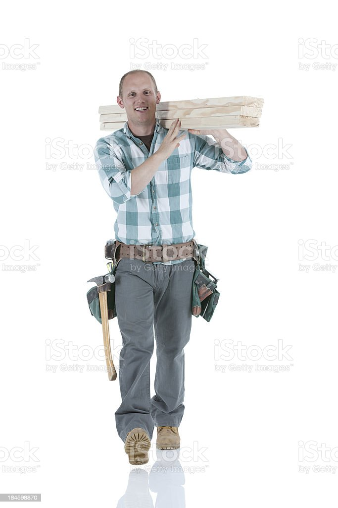 Carpenter carrying wooden planks royalty-free stock photo