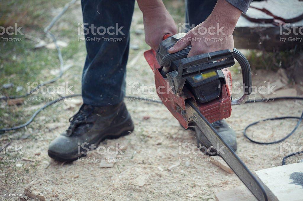Carpenter cutting log using chainsaw - closeup stock photo