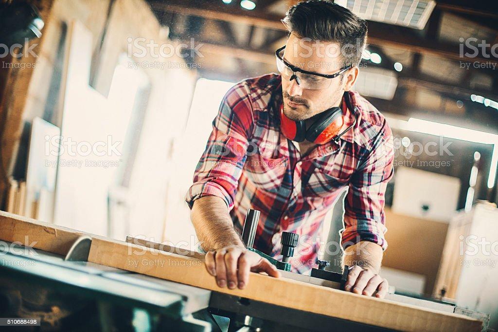 Carpenter cutting wood. stock photo