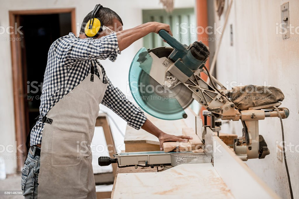 Carpenter cutting wood with a circular saw stock photo