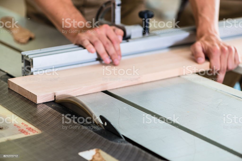 Carpenter cutting wooden board with circular saw stock photo