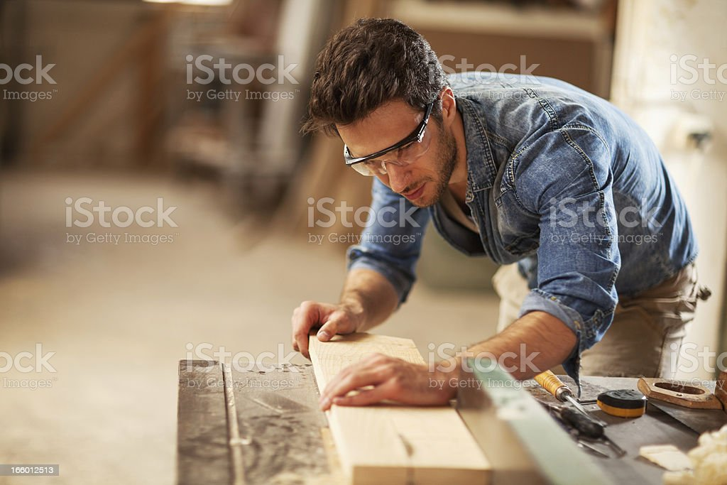 Carpenter cutting wooden plank stock photo