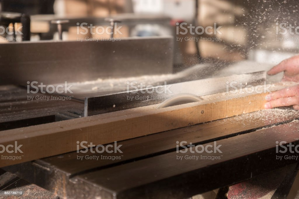 Carpenter cutting wooden plank stock photo