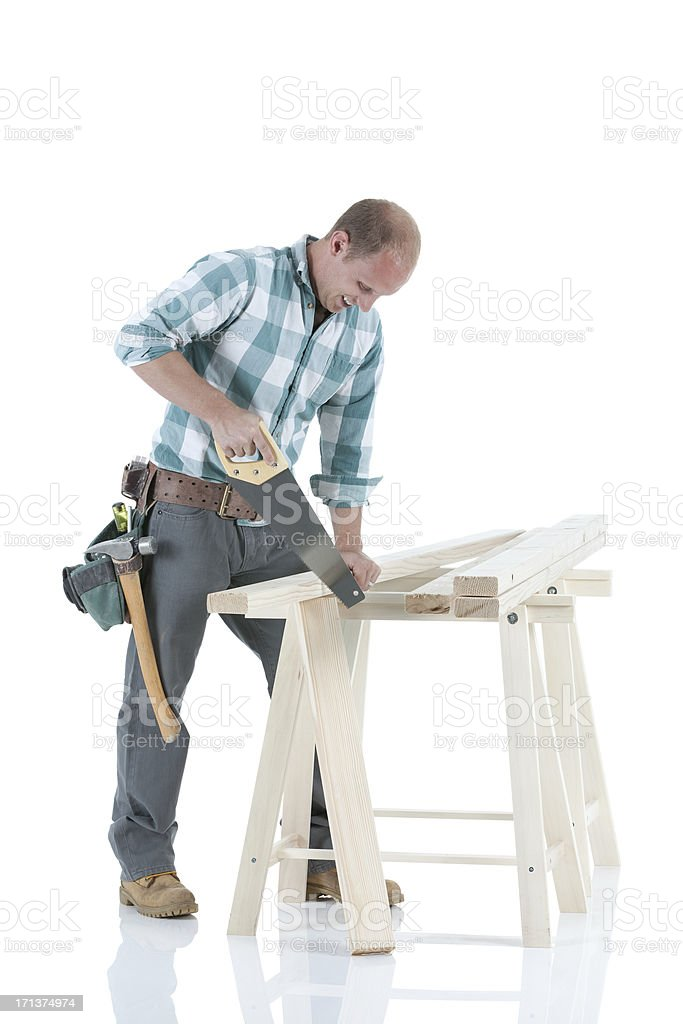 Carpenter cutting wooden plank with a saw stock photo