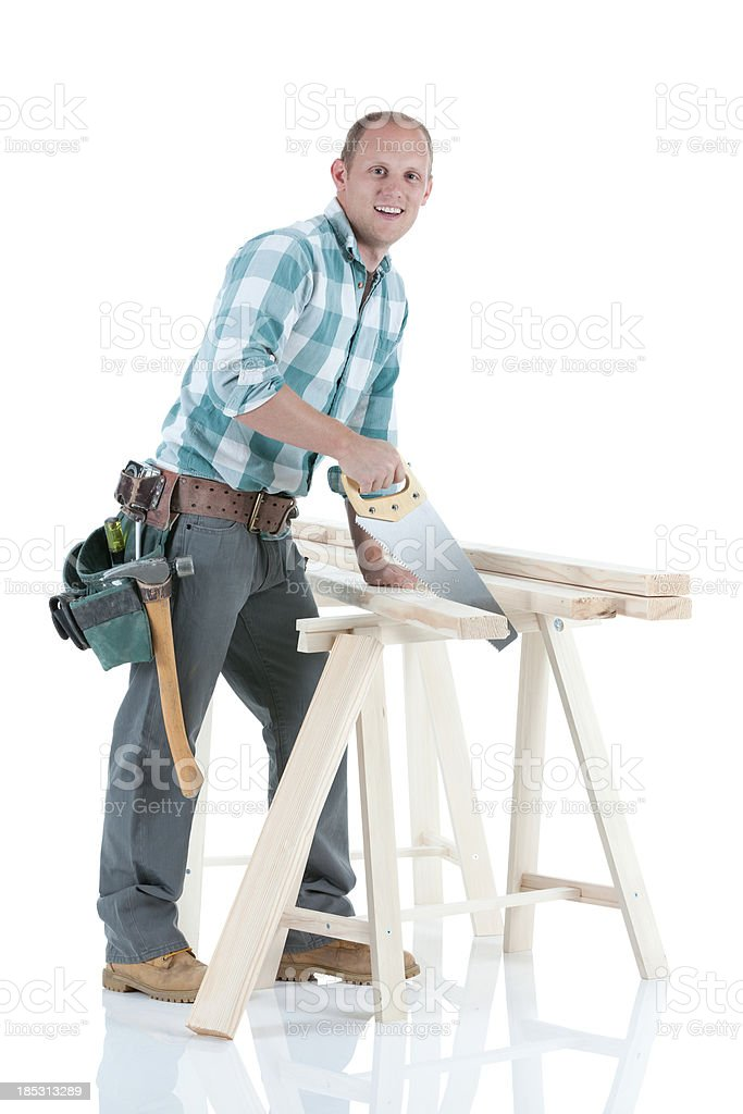 Carpenter cutting wooden planks with a saw royalty-free stock photo
