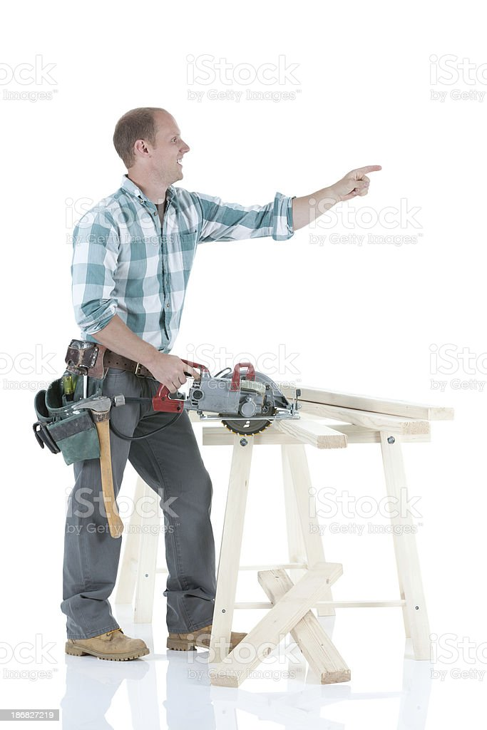 Carpenter cutting wooden planks with a saw stock photo