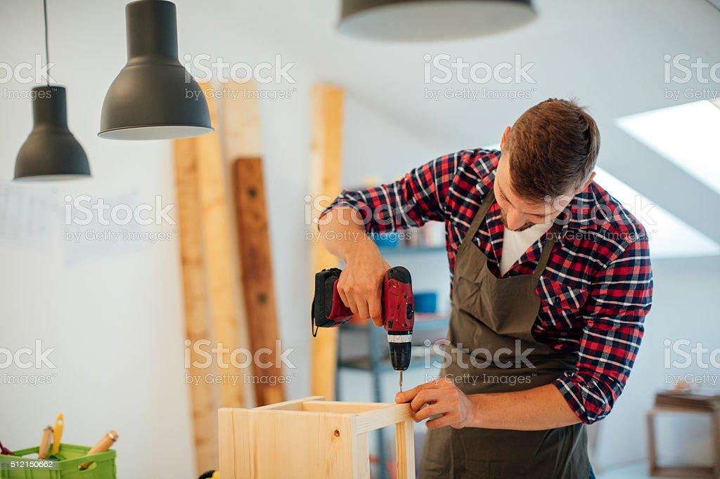 Carpenter drilling wooden plank stock photo