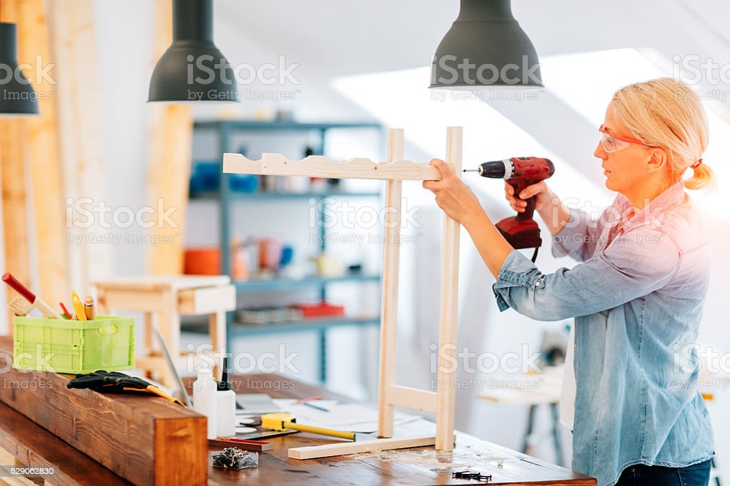 Carpenter drilling wooden plank stock photo