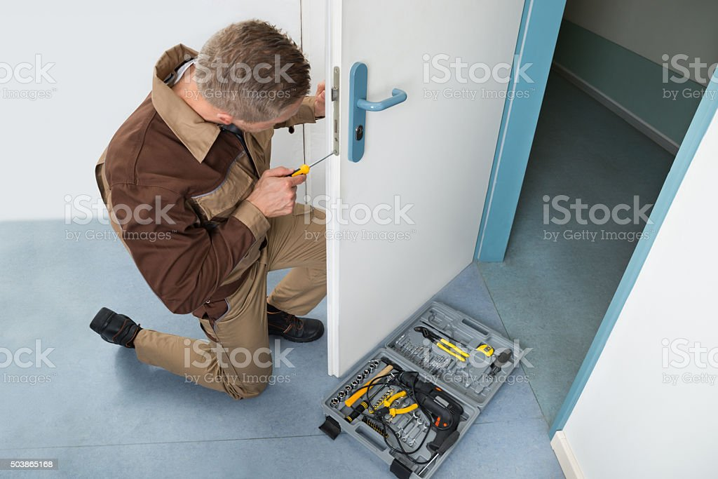 Carpenter Fixing Lock With Screwdriver stock photo
