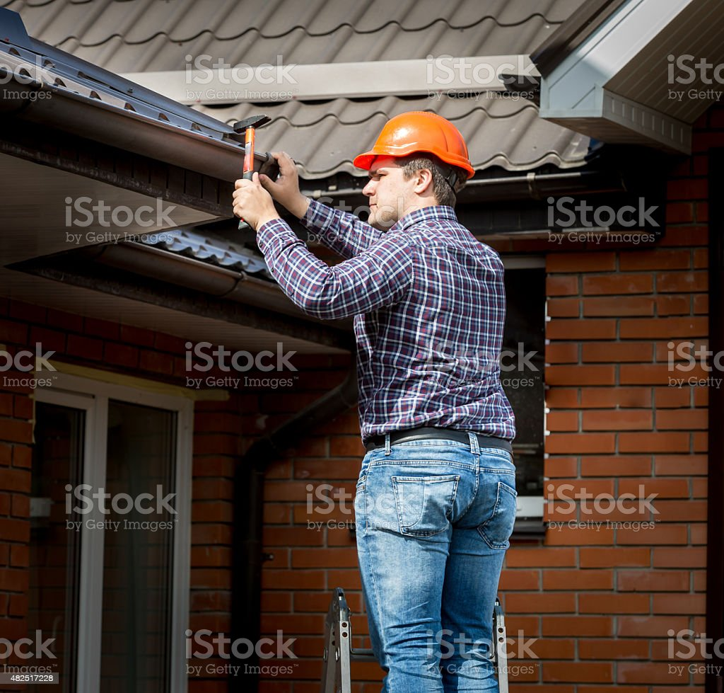 carpenter hammering roof boards with hammer stock photo