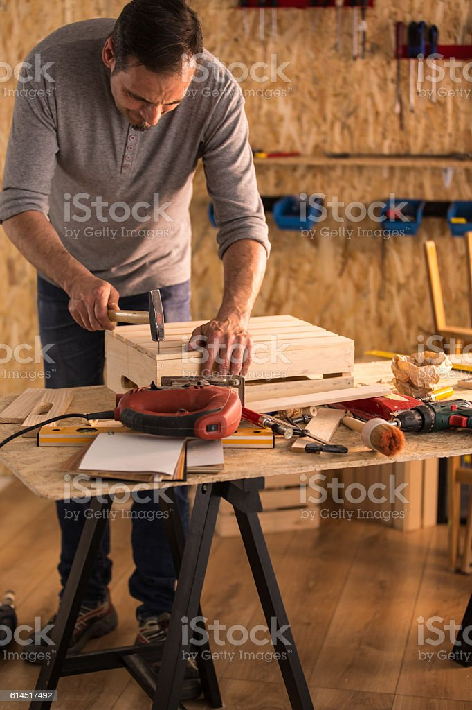 Carpenter hammers nail into a wooden crate stock photo
