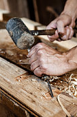 carpenter hands working with a chisel and hammer