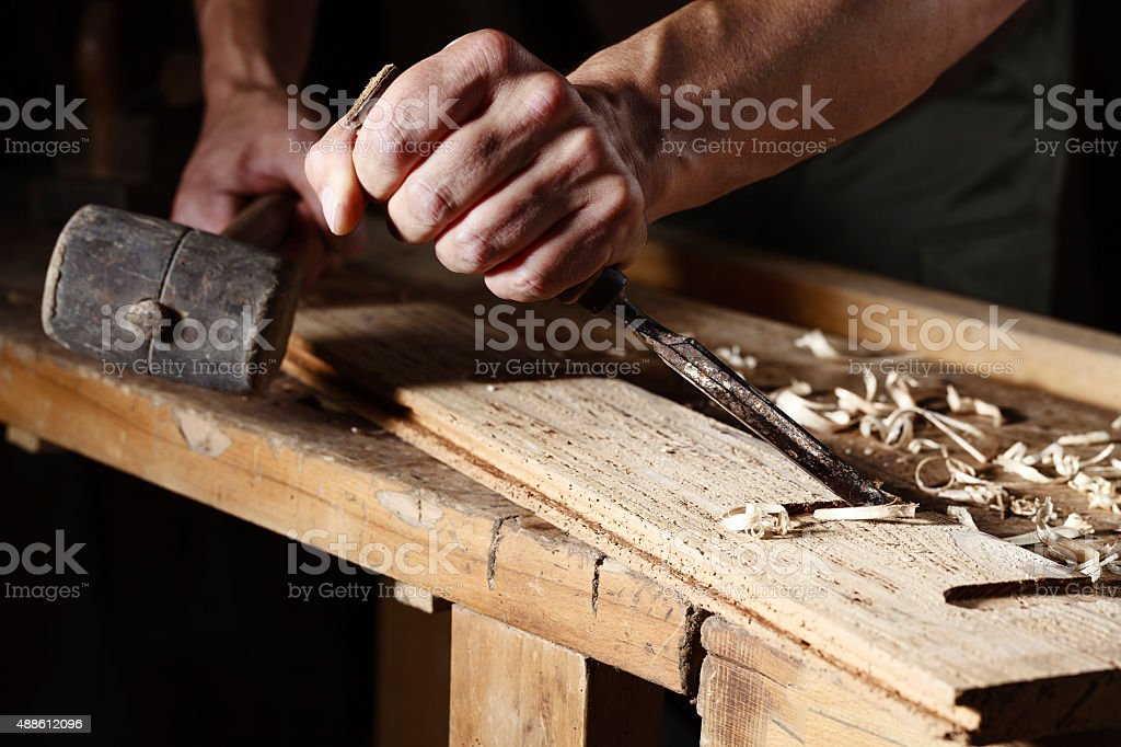 carpenter hands working with a chisel and hammer stock photo