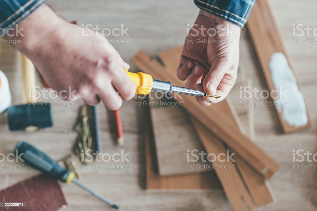 Carpenter holding a screwdriver stock photo