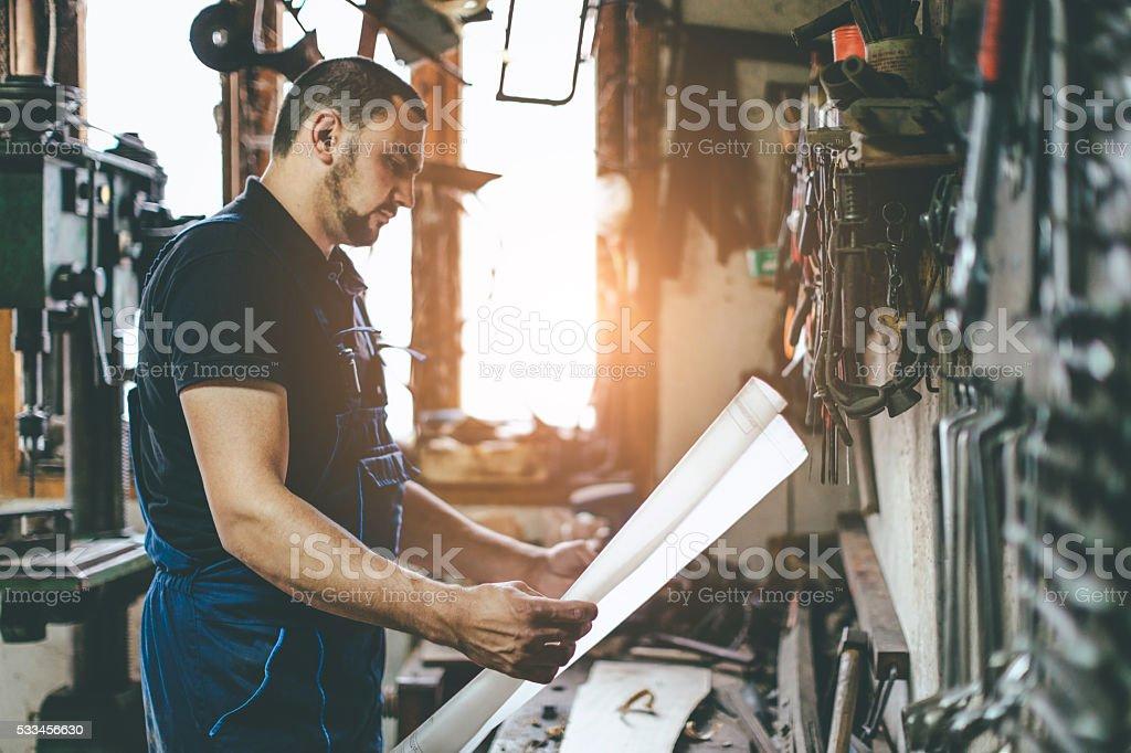 carpenter holding plans stock photo