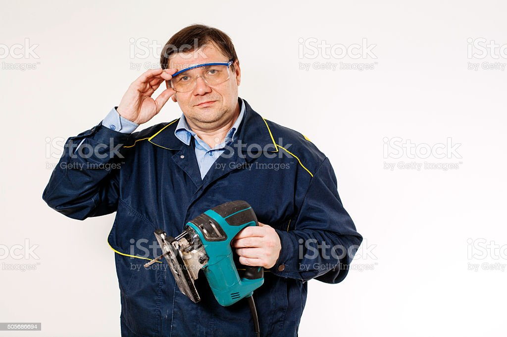 Carpenter in goggles with an electric jigsaw. Repair floor stock photo