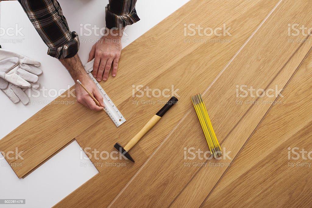 Carpenter installing a wooden flooring stock photo