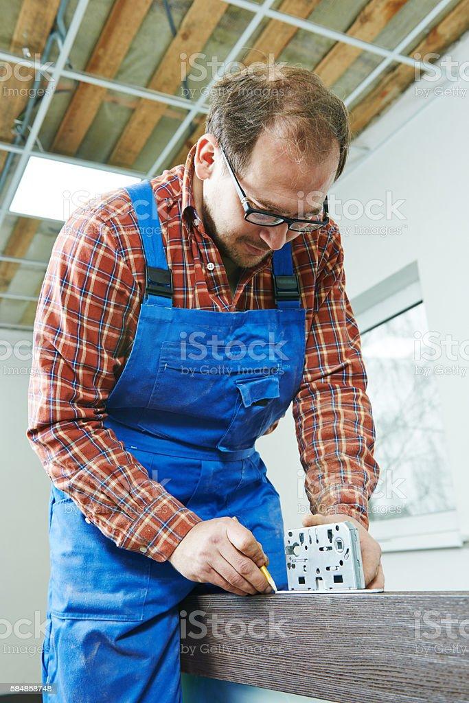 carpenter installing door lock stock photo