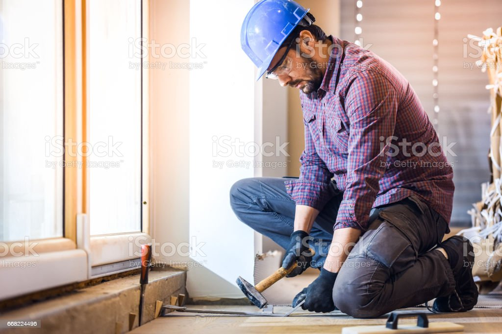 Carpenter installing hardwood floor stock photo