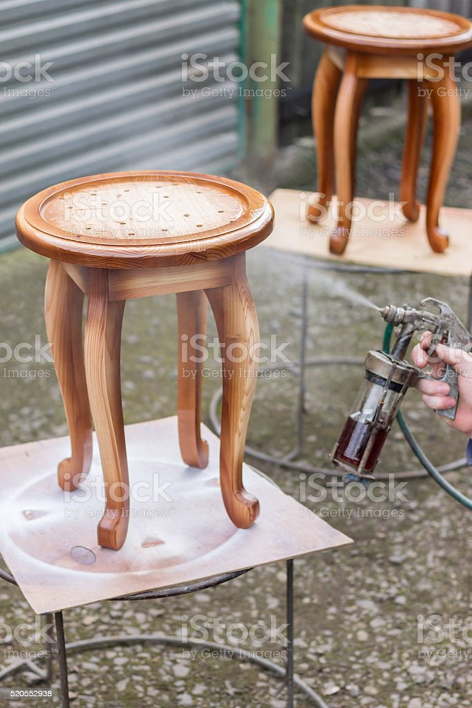 Carpenter is covering stool by lacquer stock photo