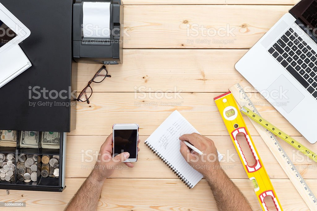 Carpenter making day end calculations stock photo