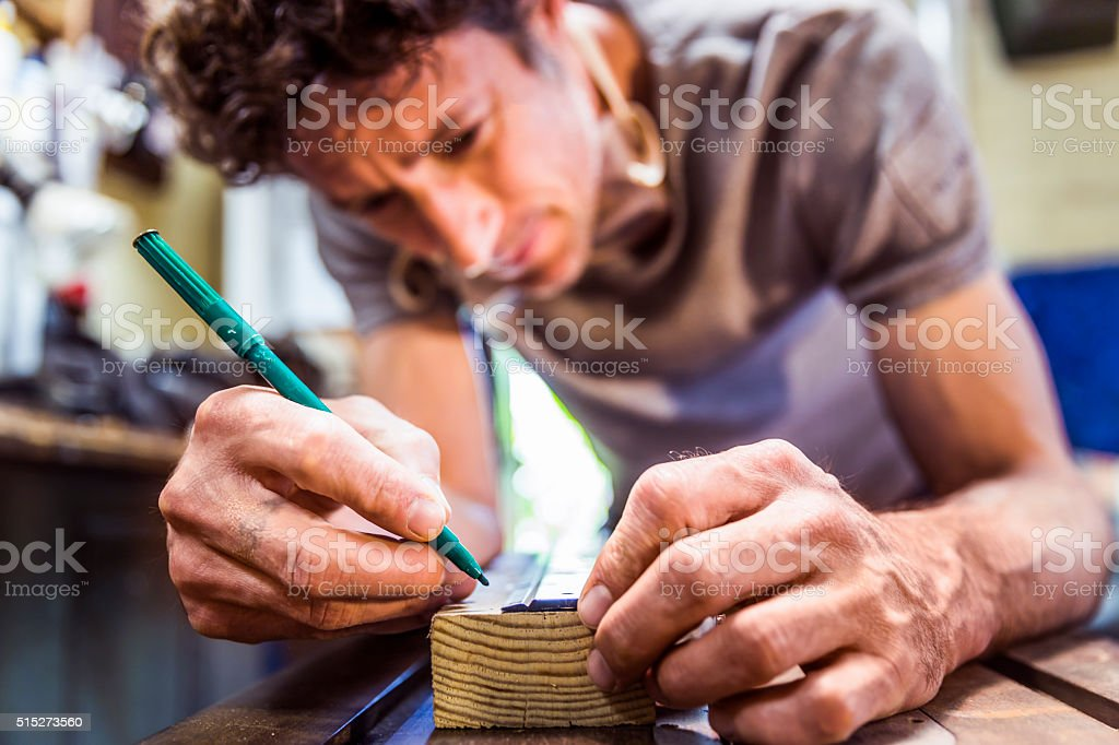 Carpenter marking on wooden plank at workplace stock photo