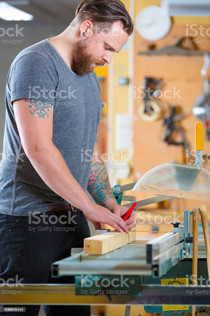 Carpenter measure the length of a wood plank before sawing stock photo