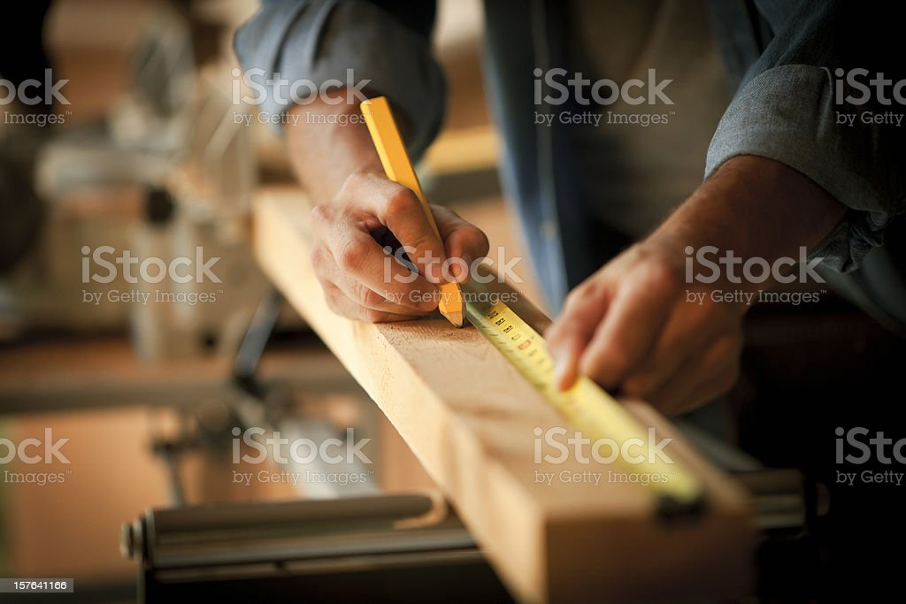 Carpenter Measuring a Wooden Plank stock photo