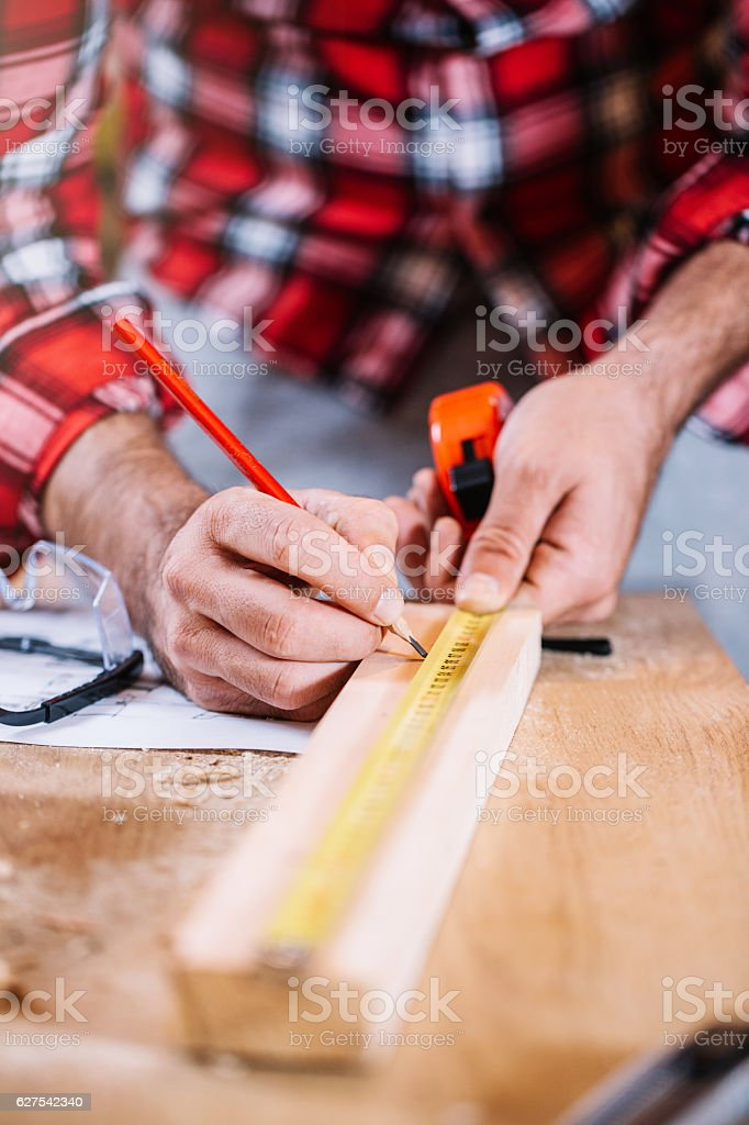 Carpenter Measuring a Wooden Plank royalty-free stock photo