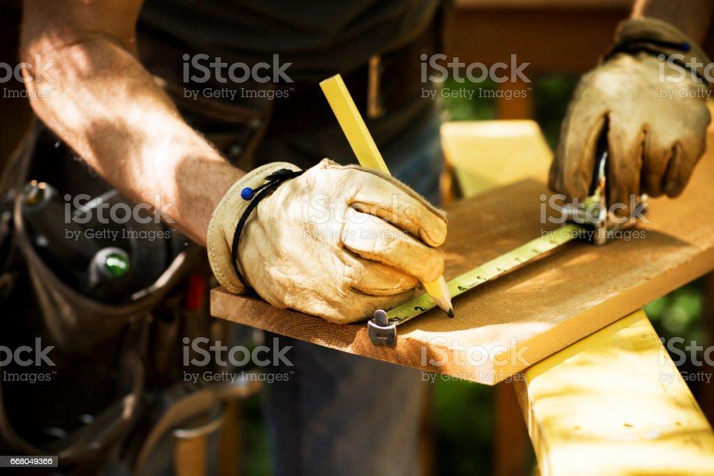 Carpenter Measuring A Wooden Plank. stock photo